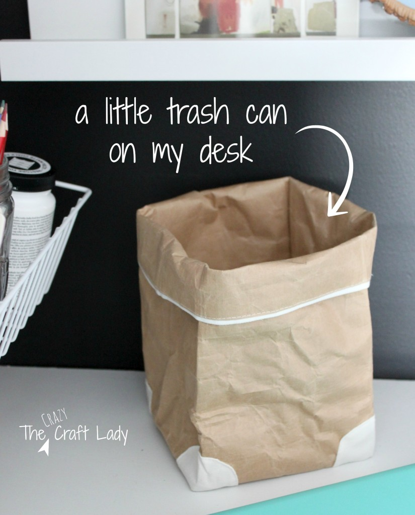 A little brown paper bag serves as a trash can on a desktop or work space for small paper scraps