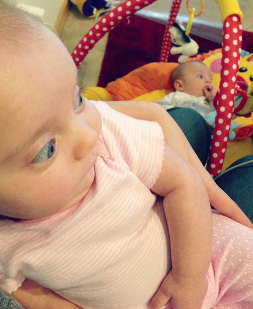 Multitasking Momma - One baby on my lap, and the other on a play mat.