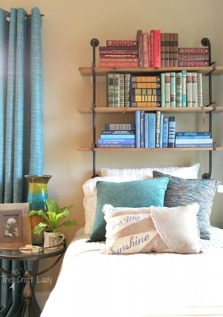 An industrial pipe bookshelf instead of a headboard.