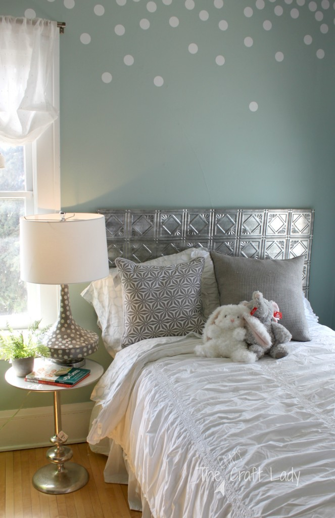 "This DIY is genius! Make a ""fake"" headboard using tin ceiling tiles. This is a beautiful little girl's bedroom full of DIY decor inspiration!"