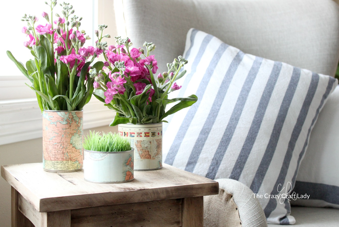 Try this upcycling craft and make tin can vases out of recycled cans and old maps. Use map paper to spruce up empty cans and make a beautiful floral centerpiece.