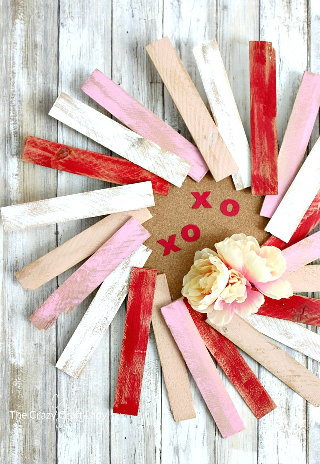 How to make a beautiful wood shim wreath. Paint inexpensive wood shims to make a fun and colorful wreath for Valentine's Day.