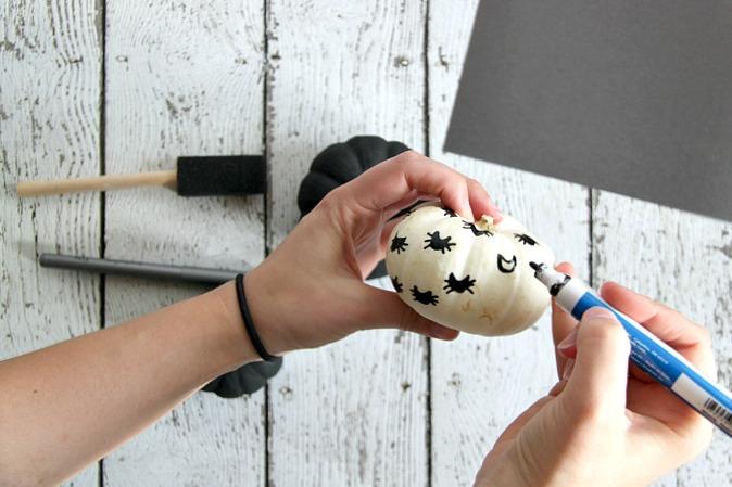 Decorating mini pumpkins with paint pens