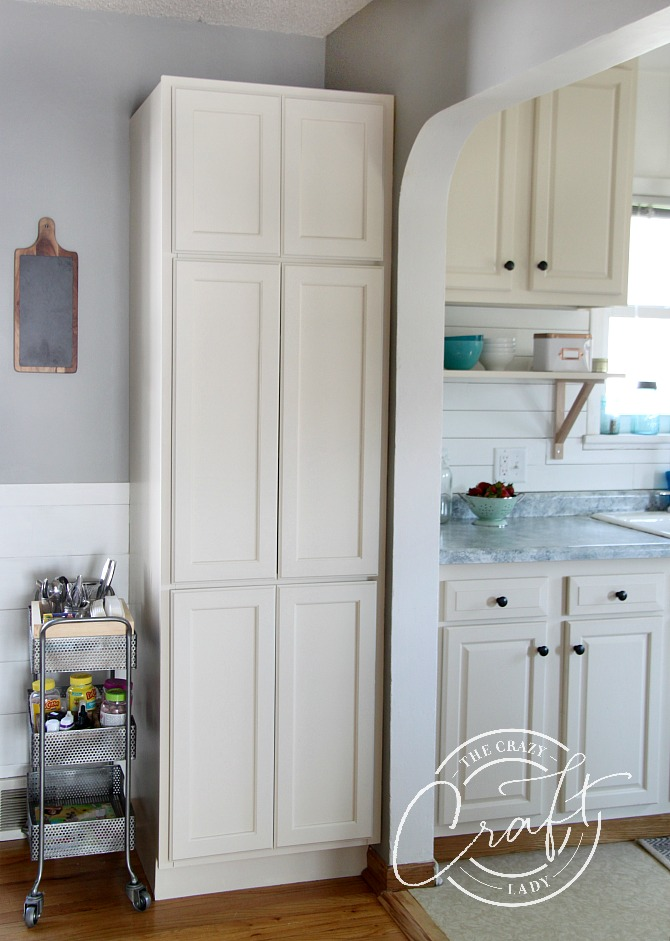 transition from dining to kitchen with arched opening and extra cabinet