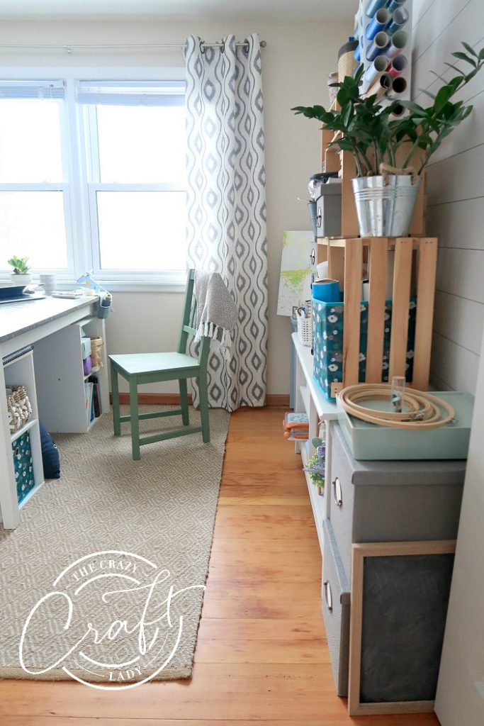 Organized craft room from The Craft lady with crate shelves, painted chair and desk, and TONS of inexpensive organizing solutions