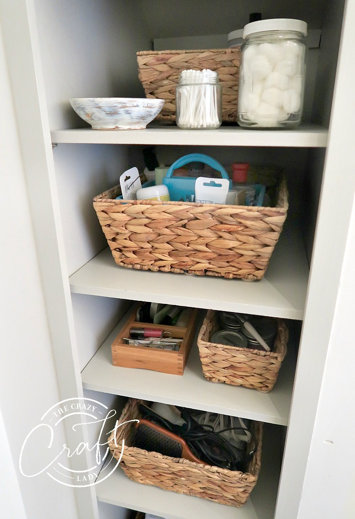 organized bathroom shelves with baskets and glass jars