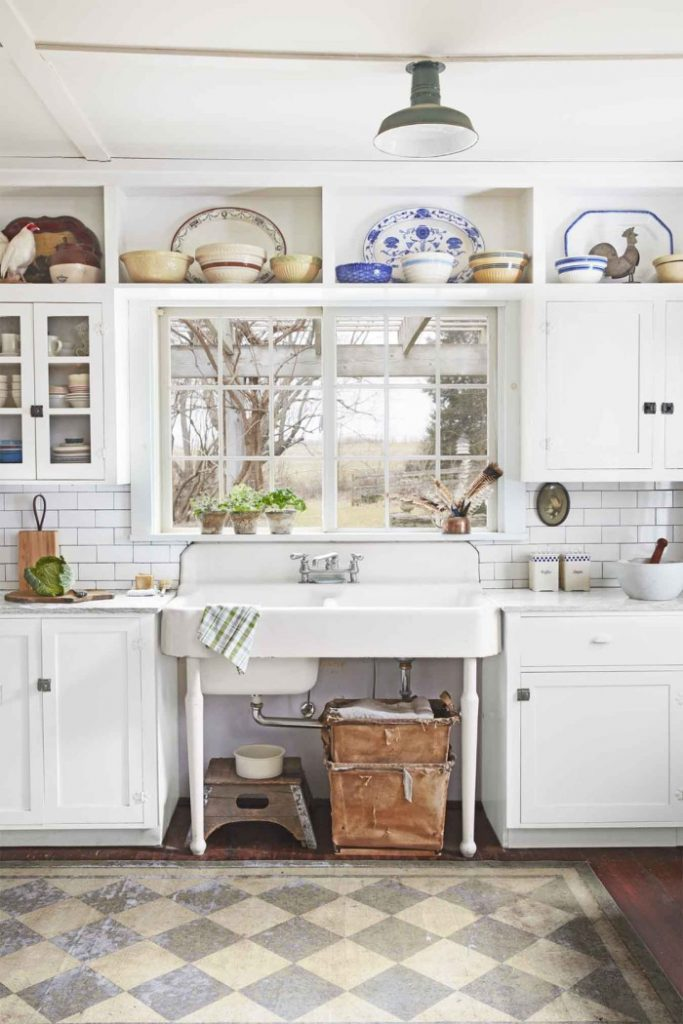 Decorate above kitchen cabinets by displaying collected potter and serving trays