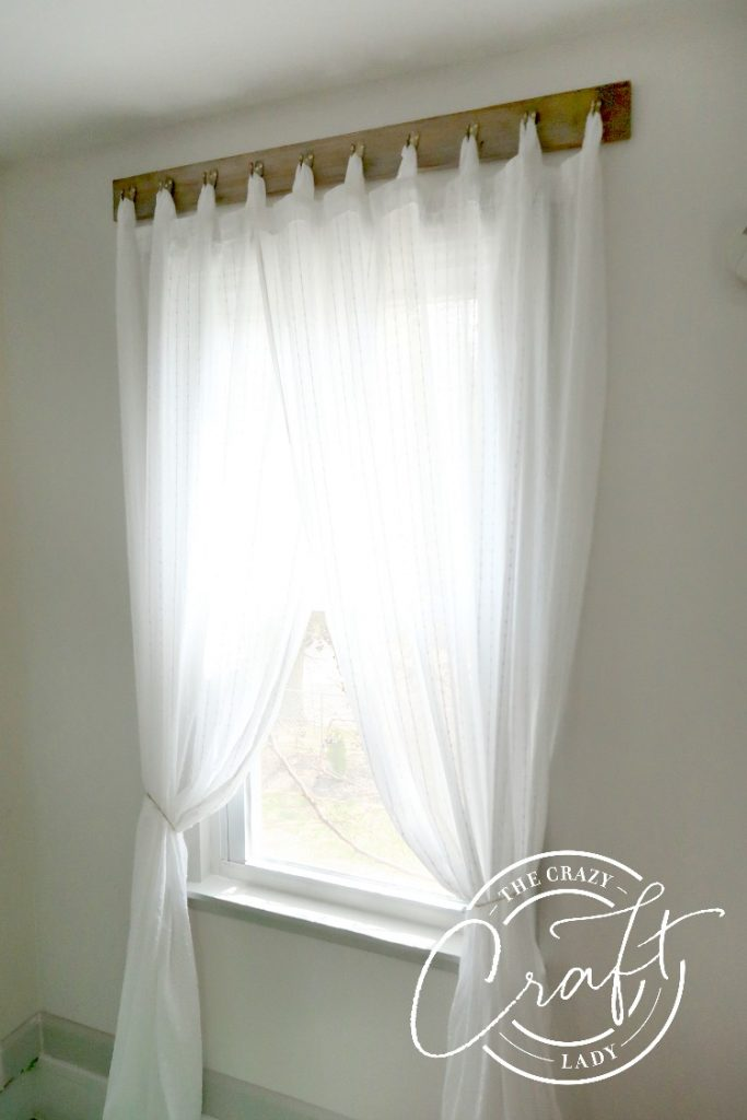 Sheer curtains hung from curtain hooks on a reclaimed board. How to distress wood and make DIY reclaimed wood curtain hooks.