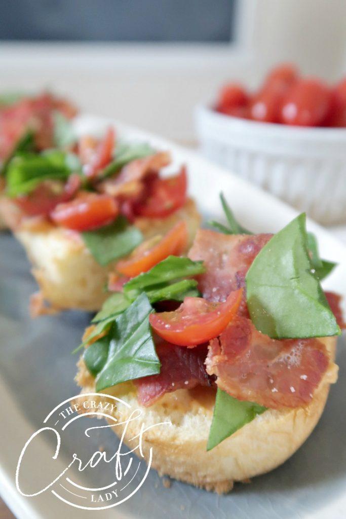 mini BLT sandwich appetizer - with brioche, hummus, bacon, spinach, and tomato